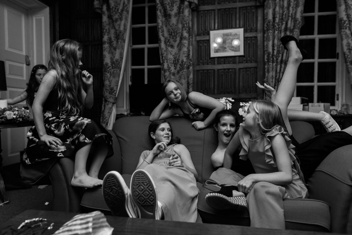 Bridesmaid with her friends playing around and sitting in various positions on a sofa in the Snug room at Gosfield Hall.
