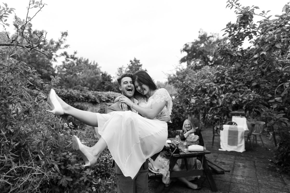 boyfriend carrying a laughing bridesmaid at Wimborne Minster wedding
