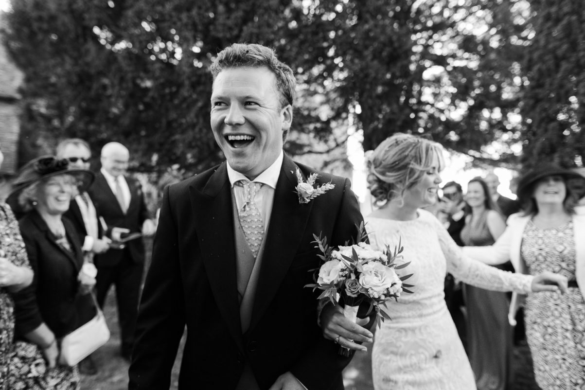 Black and white photograph of bride and groom walking through a confetti tunnel at the church in Stow Maries. The groom is in the foreground with a big smile.