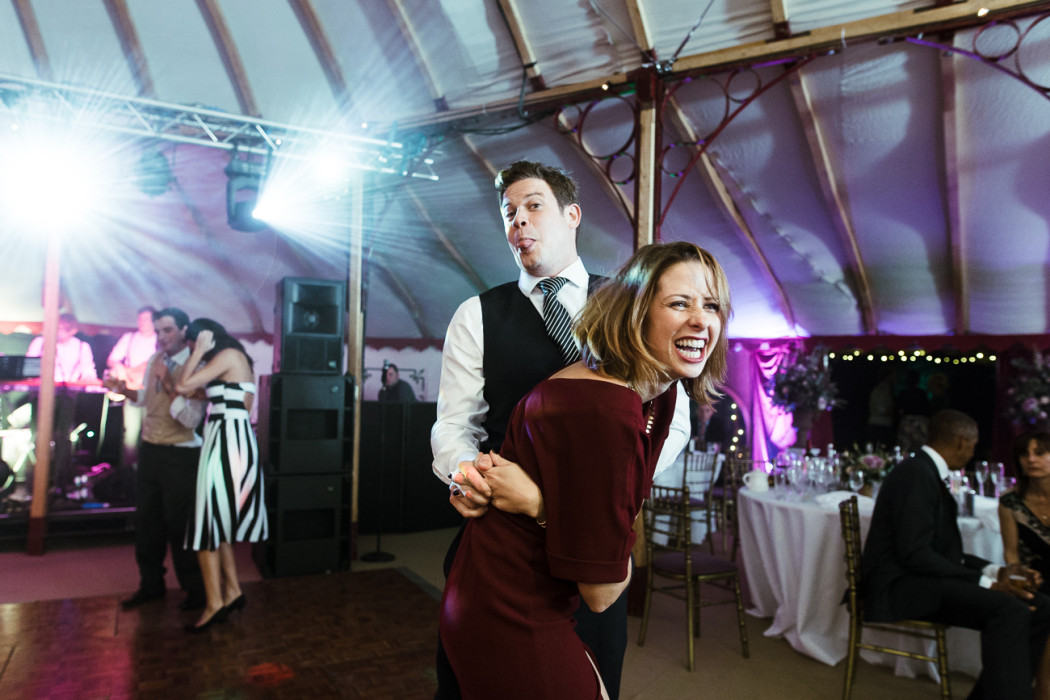 guests dancing together in a marquee at a farm wedding in Essex