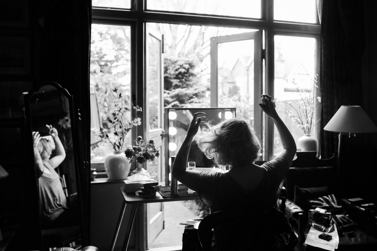 A woman doing her hair before wedding. She's looking in a mirror surrounded with light bulbs. A candid photograph.