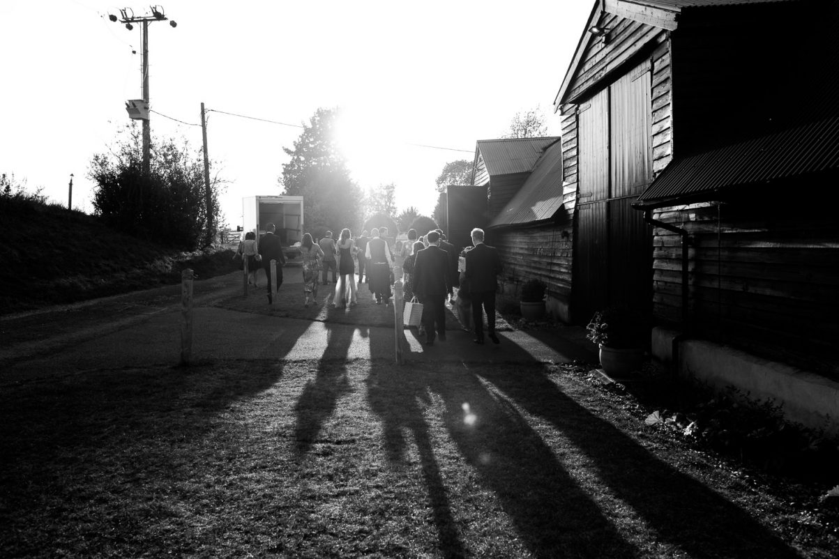 black and white photograph of guests walking into Alpheton Hall Barns in Suffolk