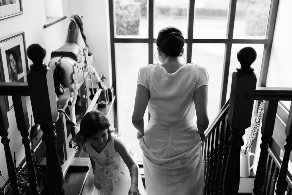 Bridesmaid walking down the stairs and flower girl coming upstairs.