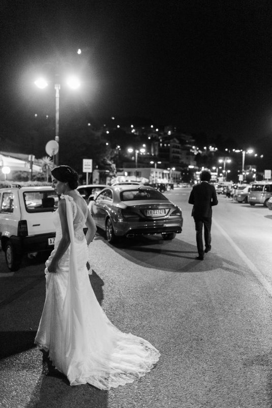 Bride is standing in the road at Via Riviera Franco Antonicelli by the port in Agropoli. The groom is walking ahead. It is nighttime.