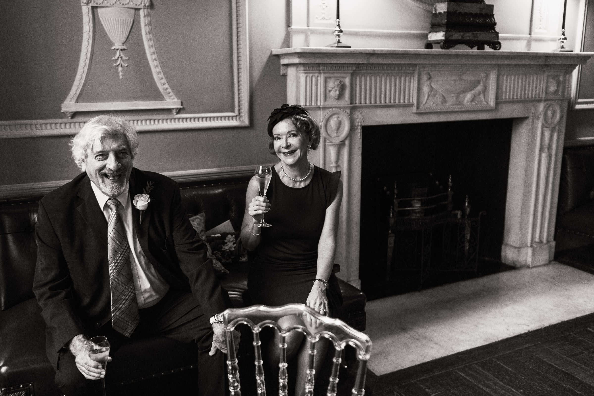 An older couple are sat on a sofa laughing at the camera. At a wedding reception at Home House in London.